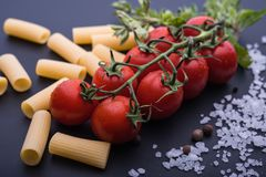 Tomato cherry, penne, salt, black background basil Italian ingredient spice vegetarian royalty free stock photo