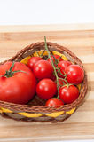 Tomato and cherry tomatoes in a basket Stock Images