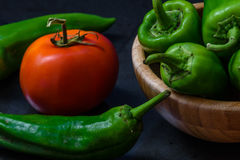 Tomato and chili pepper on a dark background. Chili pepper and tomato on a dark background. some pepper lie in a wooden bowl. the ingredients for the sauce Royalty Free Stock Images