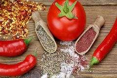 Tomato, Chili Pepper, Salt And Pepper On Rustic Wood Table. Ripe Fresh Tomato, Chili Pepper, Iodized Salt And Black Fragrant Pepper In The Small Wooden Scoops On stock photography