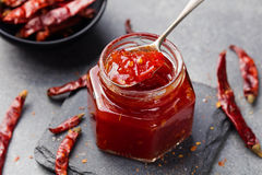 Tomato and chili sauce, jam, confiture in a glass jar on a grey stone background Stock Photos