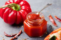 Tomato and chili sauce, jam, confiture in a glass jar on a grey stone background Royalty Free Stock Images