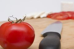 Tomato on chopping board. Tomatoes on chopping board with cheese and a knife Stock Photo