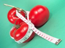 Tomato Cluster Measure. High resolution digital photo of tomatoes and a measuring tape symbolize healthy diet, cancer/disease prevention and body weight control royalty free stock photography
