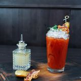 Tomato cocktail with ice decorated with arugula and a piece of bacon. Cocktail stands on a vintage wooden table in a bar. Next to a crystal bottle and a slice stock images