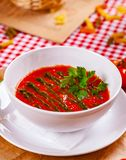 Tomato cold gazpacho soup with pesto sauce in white bowl. Close up royalty free stock image