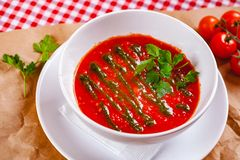 Tomato cold gazpacho soup with pesto sauce in white bowl. Close up stock images