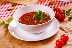 Tomato cold gazpacho soup with pesto sauce in white bowl. Close up royalty free stock photo