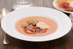Tomato cold soup with egg and jamon on white dish. On wooden background Royalty Free Stock Images