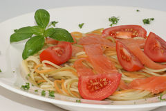Tomato and colored spaghetti Stock Images