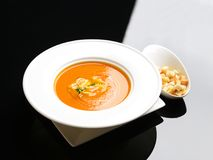 Tomato cream soup garnished with crispbread on a white and black Stock Images