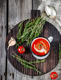 Tomato cream soup in mug and thyme on a wooden table. Royalty Free Stock Photo