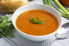Tomato cream soup in a white bowl with arugula garnish Royalty Free Stock Photos