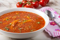 Tomato creamy soup with carrot and rice in white bowl Stock Image