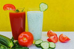 Tomato and cucumber cocktail, tomatoes and cucumbers, diet drinks on a yellow background Royalty Free Stock Images