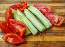 Tomato and cucumber on cuttintomato and cucumber on wood cutting boardg board Stock Image
