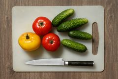 Tomato, cucumber and knife. Royalty Free Stock Photos