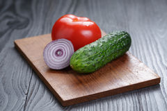 Tomato, cucumber and onion on black wood table Royalty Free Stock Photography