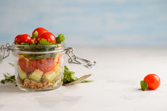 Tomato and cucumber salad in a glass jar. On a white background Stock Image