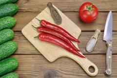 Tomato, Cucumbers, Knife And Hot Peppers On The Wood Background royalty free stock photos