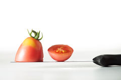 Tomato cut. Tomato cut with knife close up Stock Photo