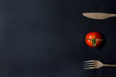 Tomato and cutlery on the table Stock Photos