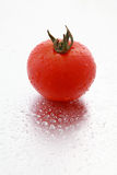 Tomato and drops. Tomato and water drops drops on the silver color bacground royalty free stock photos