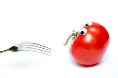 Tomato with eyes. Whole tomato with eyes and fork isolated on white Royalty Free Stock Images