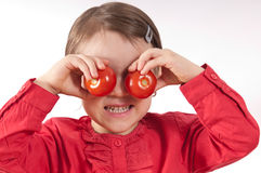 Tomato Eyes. Pre-schooler girl holding two tomatoes to her eyes royalty free stock images