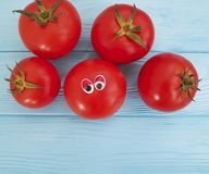 Tomato funny eyes cartoon on blue wooden positive emotion. Tomato eyes funny cartoon on blue wooden emotion Stock Photos