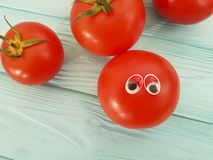 Tomato funny organic concept person eyes cartoon on blue wooden positive emotion. Tomato eyes funny organic cartoon on blue wooden emotion person cute concept Stock Image