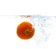 Tomato falling or dipping in water with splash Royalty Free Stock Images