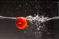 Tomato falling in water Royalty Free Stock Images