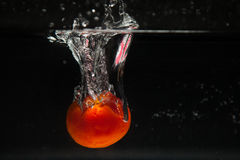 Tomato falling in water Stock Photo
