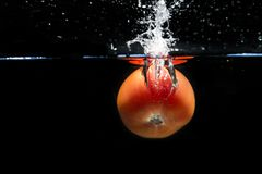 Tomato falling into the water and splashing drops on black backg Royalty Free Stock Photography
