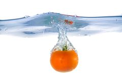Tomato fell into the water. Close-up Stock Images