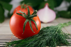 Tomato with fennel and an onions. On the back background, lying on a wooden napkin Royalty Free Stock Photography