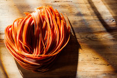 Tomato flavored linguine or tagliatelli pasta Stock Images
