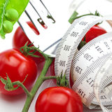 Tomato,fork ,peas and measure tape on a plate Royalty Free Stock Photo