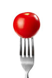 Tomato on a fork. On white background Stock Images