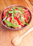 Tomato with fresh arugula salad on the wooden table Stock Image