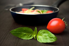 Tomato with fresh basil and a frying pan Stock Photos