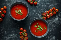 Tomato and fresh basil soup with garlic, cracked papper corns, served with cream and sourdough bread Royalty Free Stock Photo