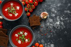 Tomato and fresh basil soup with garlic, cracked papper corns, served with cream and sourdough bread.  Stock Photography