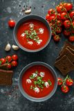 Tomato and fresh basil soup with garlic, cracked papper corns, served with cream and sourdough bread Stock Photos