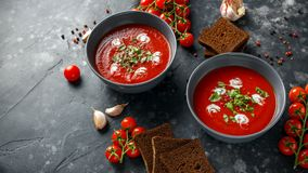 Tomato and fresh basil soup with garlic, cracked papper corns, served with cream and sourdough bread Royalty Free Stock Images