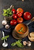 Tomato and fresh basil soup with garlic, served with cream royalty free stock images