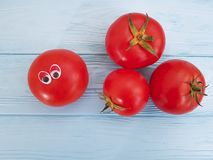 Tomato funny cartoon on blue wooden. Funny Stock Image