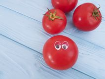 Tomato funny cartoon on blue wooden positive emotion. Tomato funny cartoon on blue wooden funny emotion positive Royalty Free Stock Photo