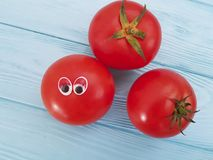 Tomato funny cartoon on blue wooden positive. Tomato funny cartoon on blue wooden funny    positive Royalty Free Stock Photography